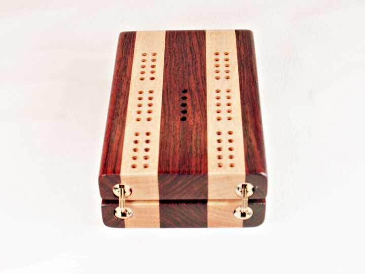Bubinga and Maple Travel Cribbage Board opened up showing the the hidden hinges that can't be seen when the board is being played.